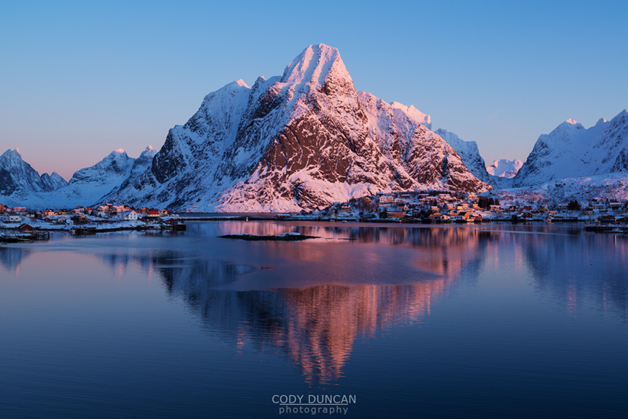 Olstind mountain peak glows pink in winter sunrise, Reine, Lofoten Islands, Norway