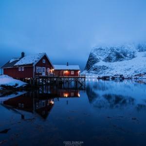Traditional Rorbu cabin reflects in fjord in evening light, Valen, Reine, Moskenesøy, Lofoten Islands, Norway