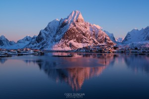 snow covered Olstind mountain peak glows pink in winter sunrise, Reine, Lofoten Islands, Norway