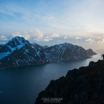 photographer on summit of Offersoykammen with Flakstadoy in background, Lofoten Islands, Norway