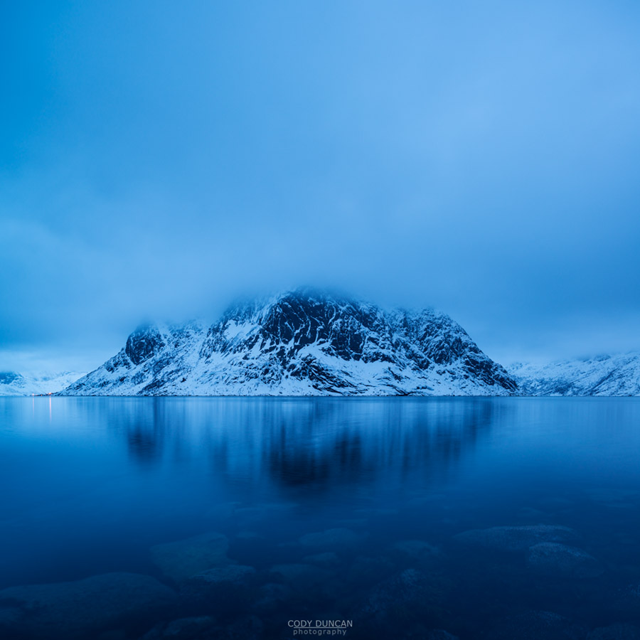 Heavy clouds conceal summit of Olstind mountain peak rising from fjord, Reine, Moskenesøy, Lofoten Islands, Norway