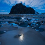 Full moon shines in night sky above mountain peak, Eggum, Lofoten Islands, Norway