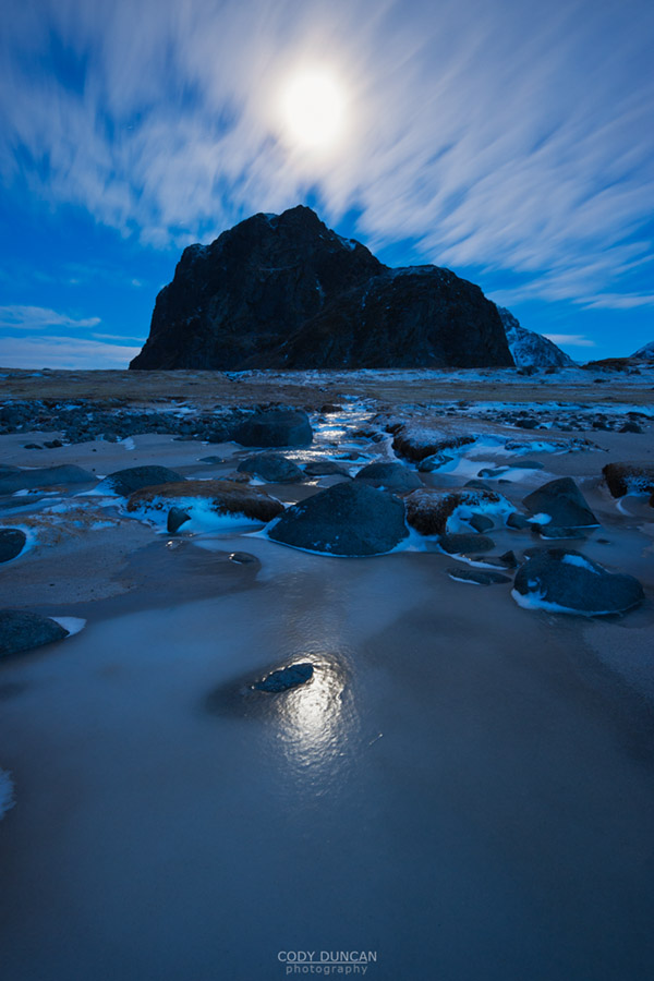 Full moon shines in night sky above mountain peak, Eggum, Lofoten Islands, Norway