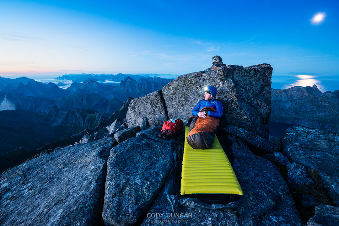 Open air mountain bivy on rocky summit of Hermannsdalstinden, Moskenesoy, Lofoten Islands, Norway