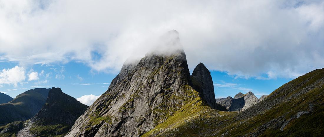 Clouds conceal dramatic mountain peak of Kråkhammartind, Moskenesoy, Lofoten Islands, Norway
