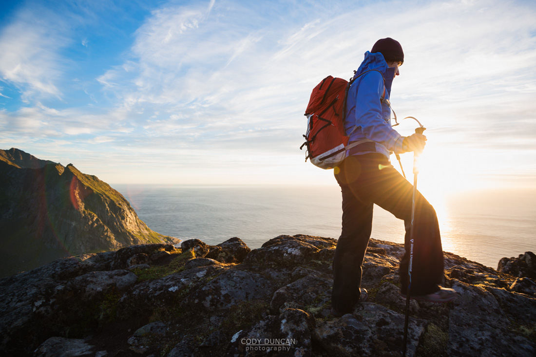 Female hiker hiking in Evening summer sun on summit of Ryten, Moskenesoy, Lofoten Islands, Norway
