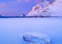 Block of ice on frozen Haukland beach in winter, Vestvagøy, Lofoten islands, Norway