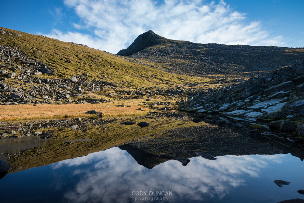 Kroktind (707m) mountain peak reflects in small lake, Austvagoy, Lofoten Islands, Norway