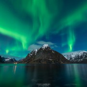 Northern Lights - Aurora Borealis shine in sky over Olstind mountain peak and fjord near Reine, Moskenesøy, Lofoten Islands, Norway