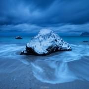 Waves wash over snow covered rock in winter at Myrland beach, Flakstadøy, Lofoten Islands, Norway