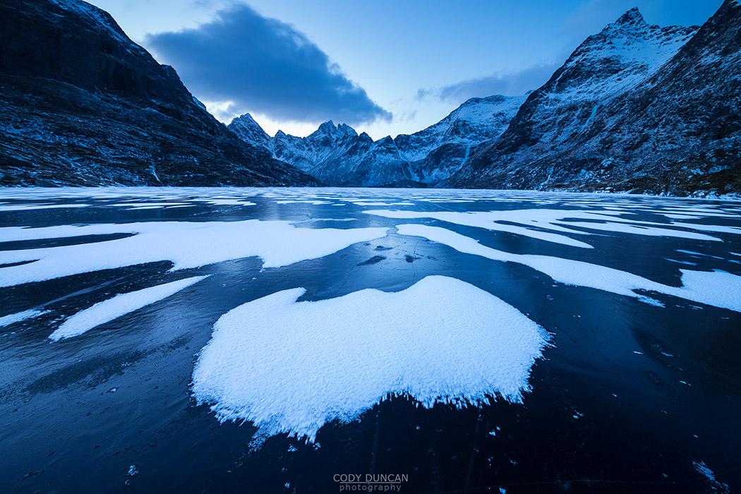 Patterns of snow cover black ice of Lake Ågvatnet in winter, Å I Lofoten, Moskenesøy, Lofoten Islands, Norway