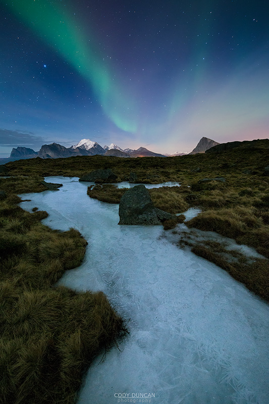 Northern Lights - Aurora Borealis shine in sky over frozen ice river and mountain landscape, Flakstadøy, Lofoten Islands, Norway