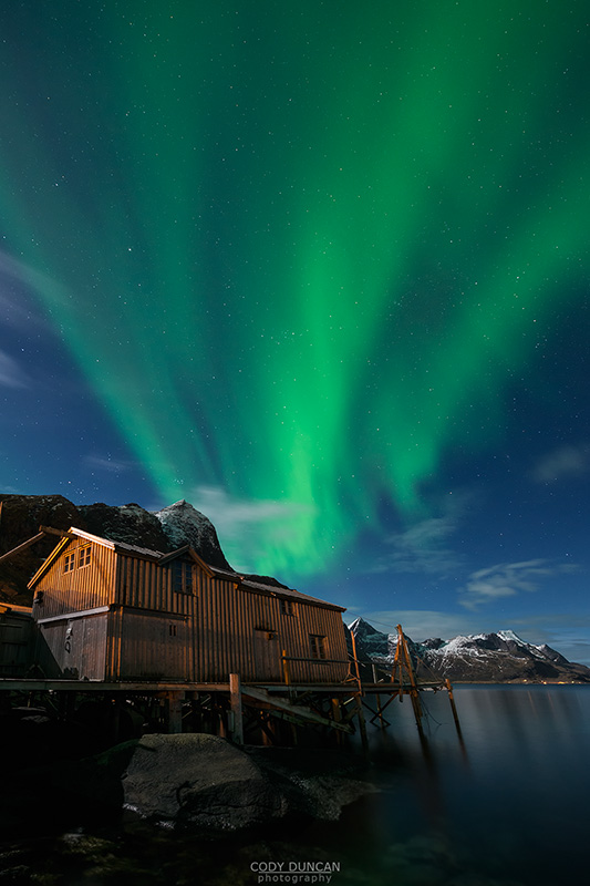 Northern Lights - Aurora Borealis shine in sky over abandoned Rorbu cabin, Valen, near Reine, Moskenesøy, Lofoten Islands, Norway
