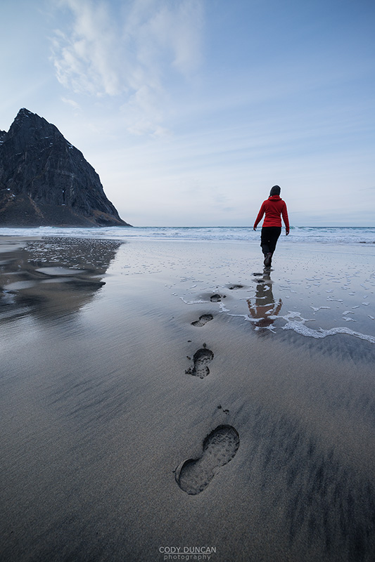 Person leaves footpints in sand at scenic Kvalvika beach, Moskenesøy, Lofoten Islands, Norway