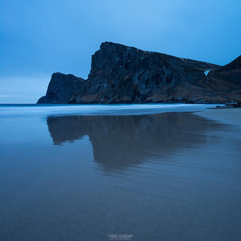 Mountain peaks rise over empty sands at Kvalvika beach, Moskenesøy, Lofoten Islands, Norway