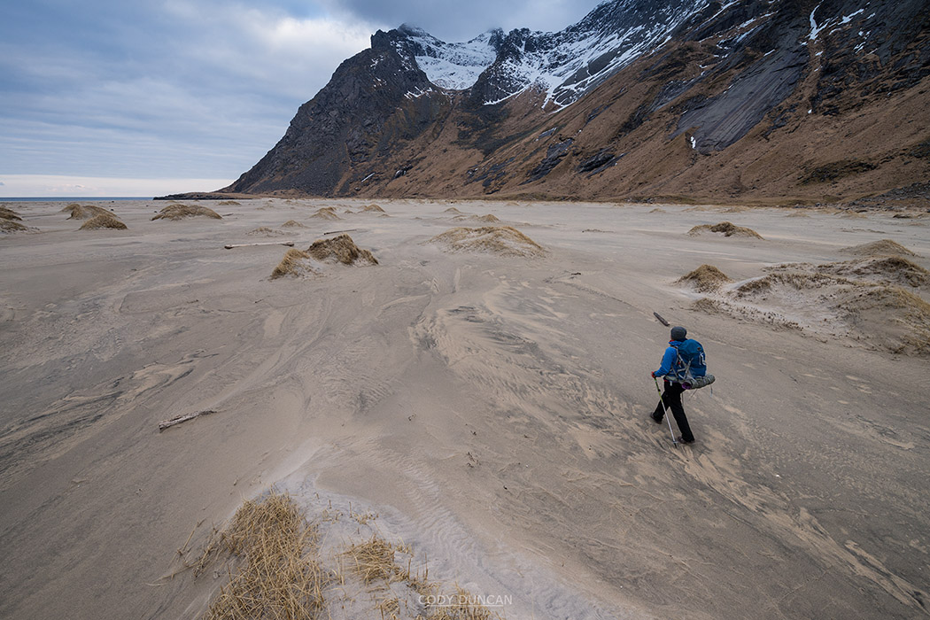 hiker hiking across sand at Horseid beach, Moskenesøy, Lofoten Islands, Norway