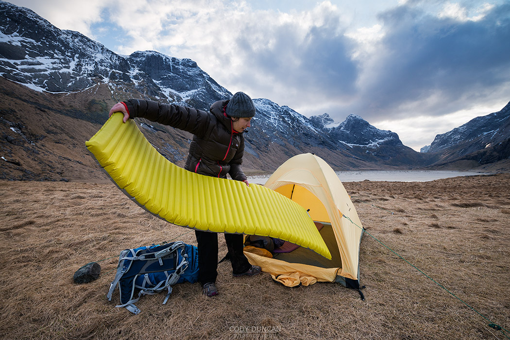 Female hiker sets up tent on wild camping trip to Horseid beach, Moskenesøy, Lofoten Islands, Norway