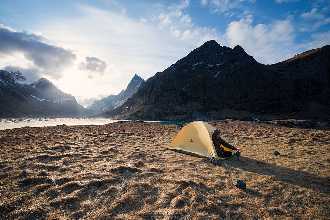 Female backpacker takes in view from tent while camping at Horseid beach, Moskenesøy, Lofoten Islands, Norway
