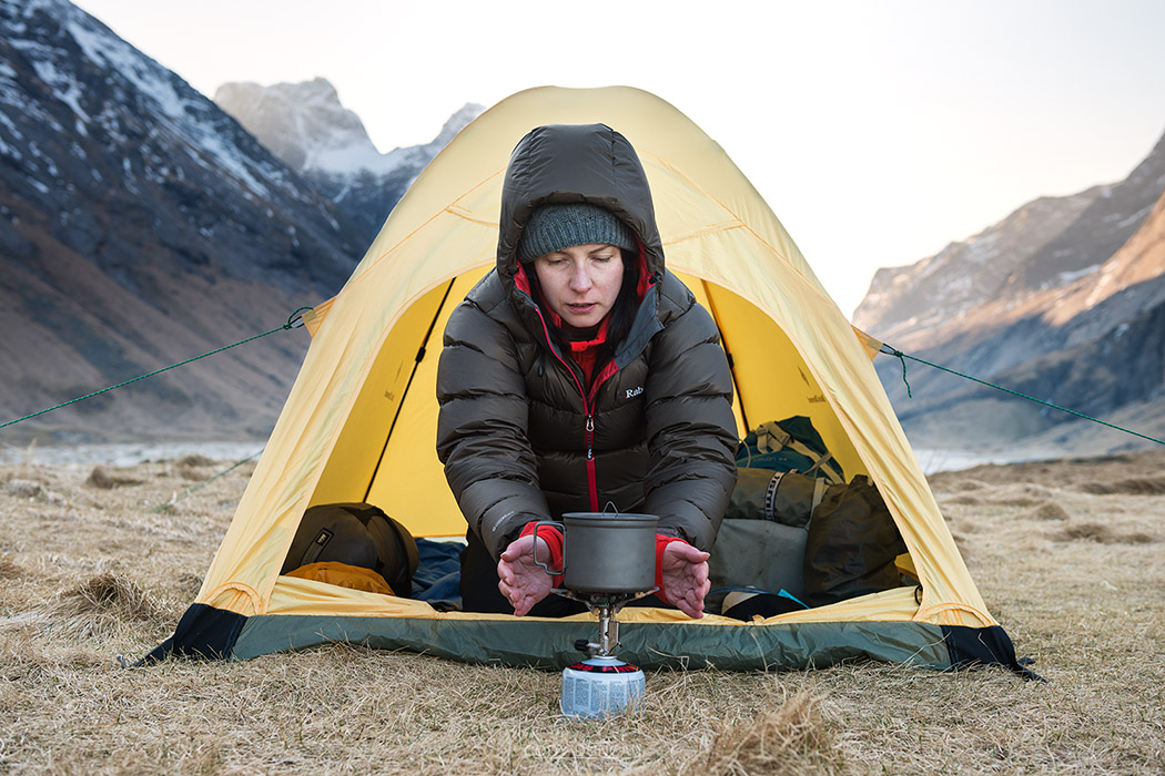 Warming hands with stove on cold morning wild camping at Horseid beach, Moskenesøy, Lofoten Islands, Norway