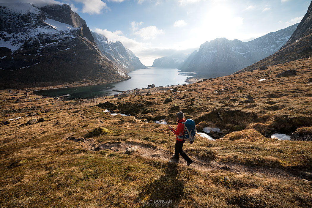 Female hiker descending trail to catch ferry at village of Kjerkfjord, Moskenesøy, Lofoten Islands, Norway