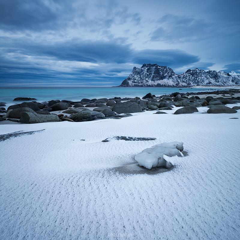 Dusting of snow covers sand at Uttakleiv beach, Vestvågøy, Lofoten Islands, Norway
