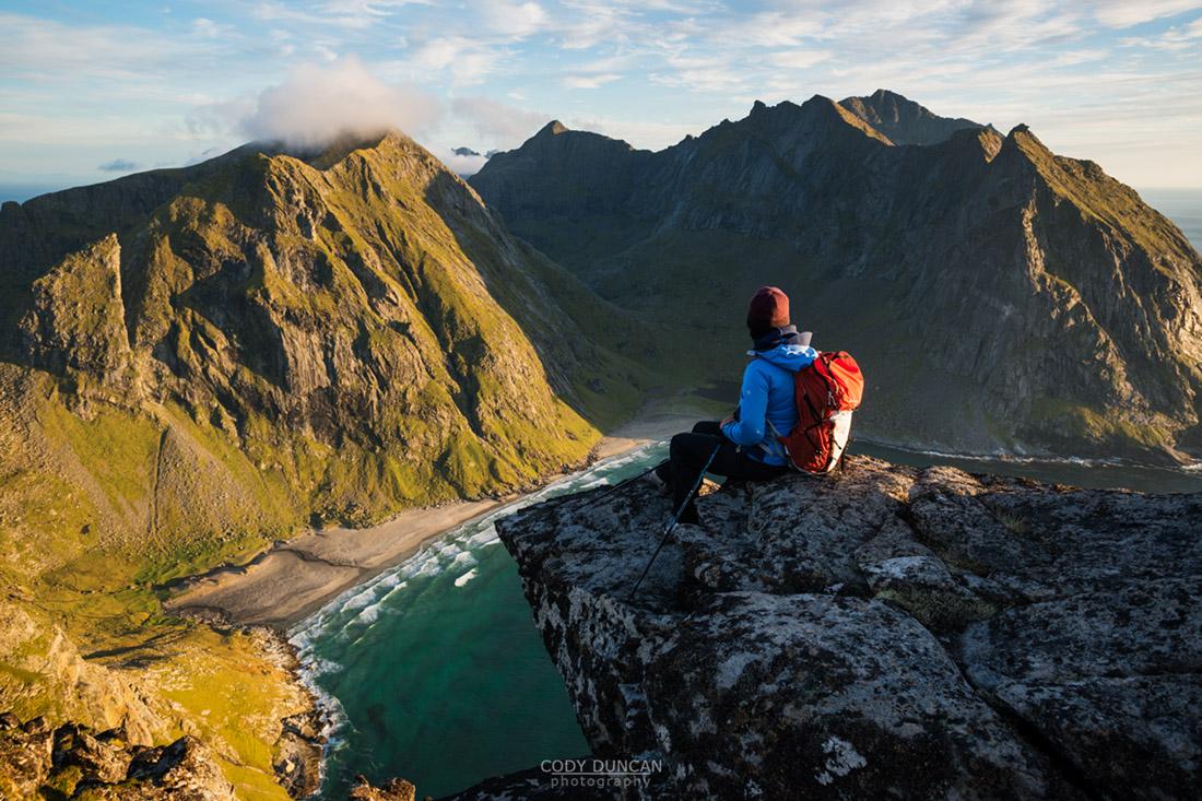 hiker enjoying view of Kvalvika beach from near summit of Ryten, Moskenesoy, Lofoten Islands, Norway