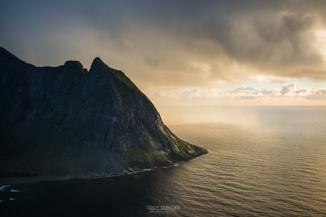 Mountain peak rises from sea as viewed from Ryten, Lofoten Islands, Norway