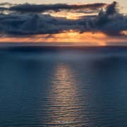 Late summer sun low on horizon over Norwegian sea, Lofoten Islands, Norway