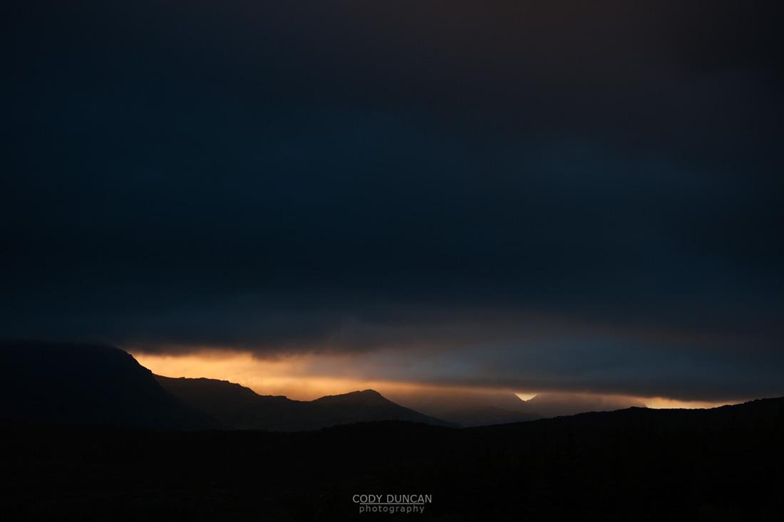 Ray of light silhouettes stormy mountain landscape, Vestvagoy, Lofoten islands, Norway