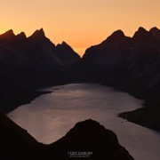 Sunset behind rugged mountain peaks and Kjerkfjord from Reinebringen peak, Reine, Lofoten islands, Norway