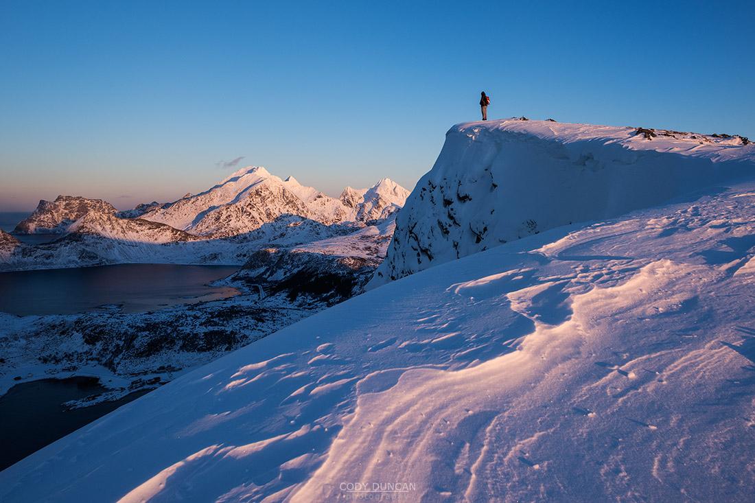 Person stands on snow covered summit of Offerøykammen in winter, Vestvågøy, Lofoten Islands, Norway