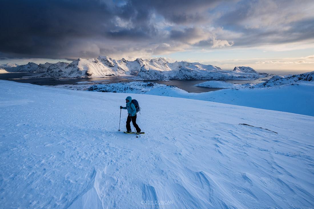 Female hiker with snowshoes hiking towards summit of Ryten, Moskenesøy, Lofoten Islands, Norway