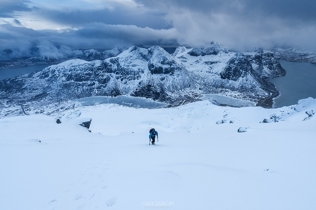 Winter climber ascending steep snow covered slopes towards summit of Hustind, Flakstadøy, Lofoten Islands, Norway
