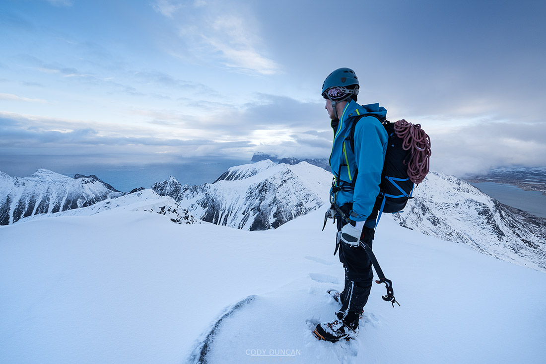 Hiker on winter summit of Hustind mountain peak, Flakstadøy, Lofoten Islands, Norway