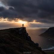 Female hiker watches midnight sun over sea from Nonstind mountain peak, Vestvågøy, Lofoten Islands, Norway