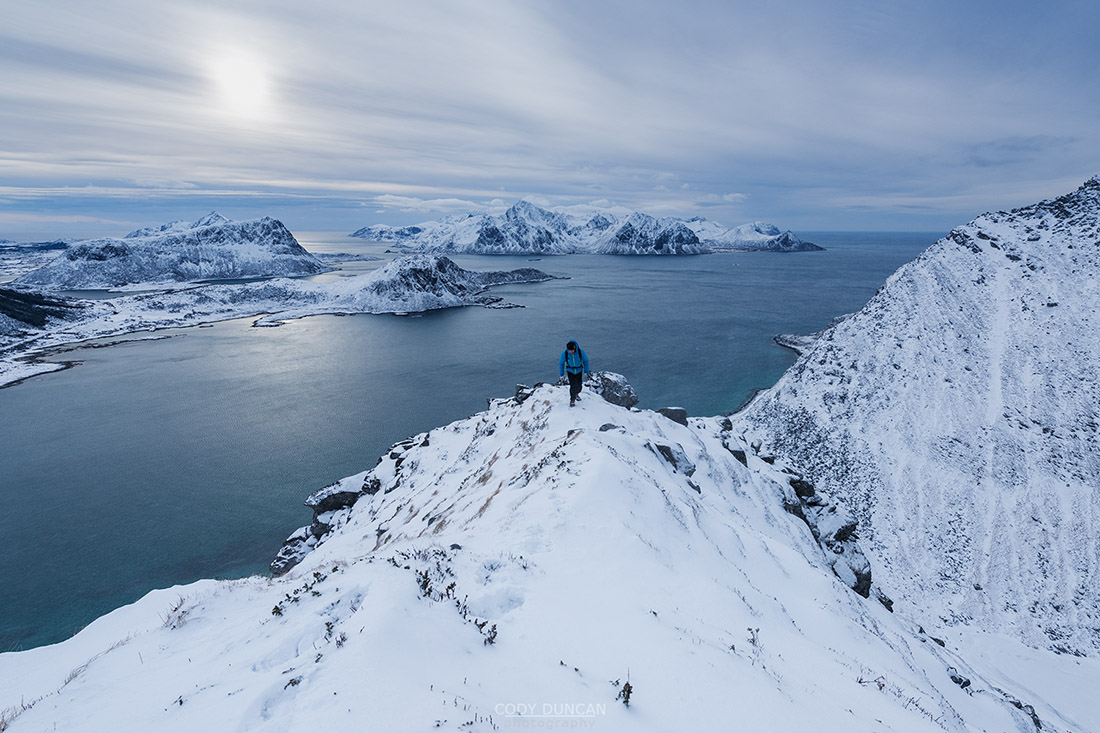 Hiker on winter ascent of Mannen mountain peak, Vestvågøy, Lofoten Islands, Norway