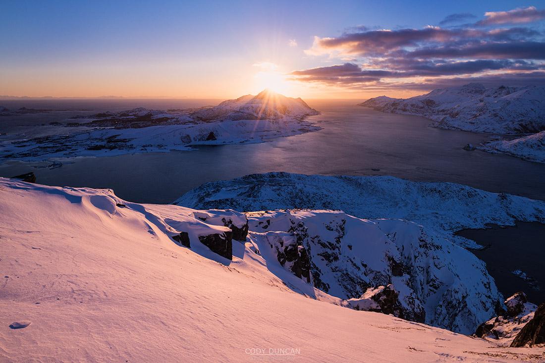 Low winter sun in January over coastal mountain landscape from Offersøykammen, Vestvågøy, Lofoten Islands, Norway