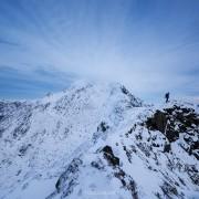 Hiker descending wintry ridge from summit of Mannen mountain peak, Vestvågøy, Lofoten Islands, Norway