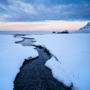 Small river running through snow on Skagsanden beach, Flakstadøy, Lofoten Islands, Norway
